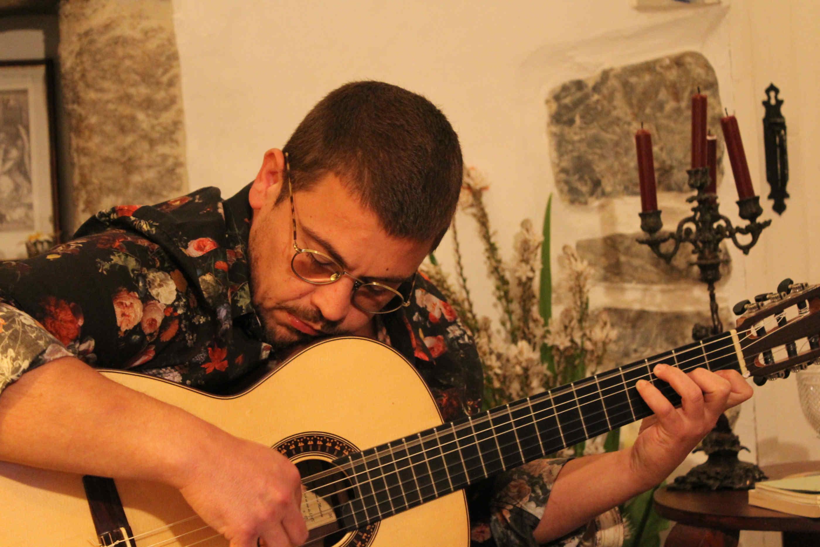 Ricardo Ribeiro a tocar violão em um ambiente domiciliar