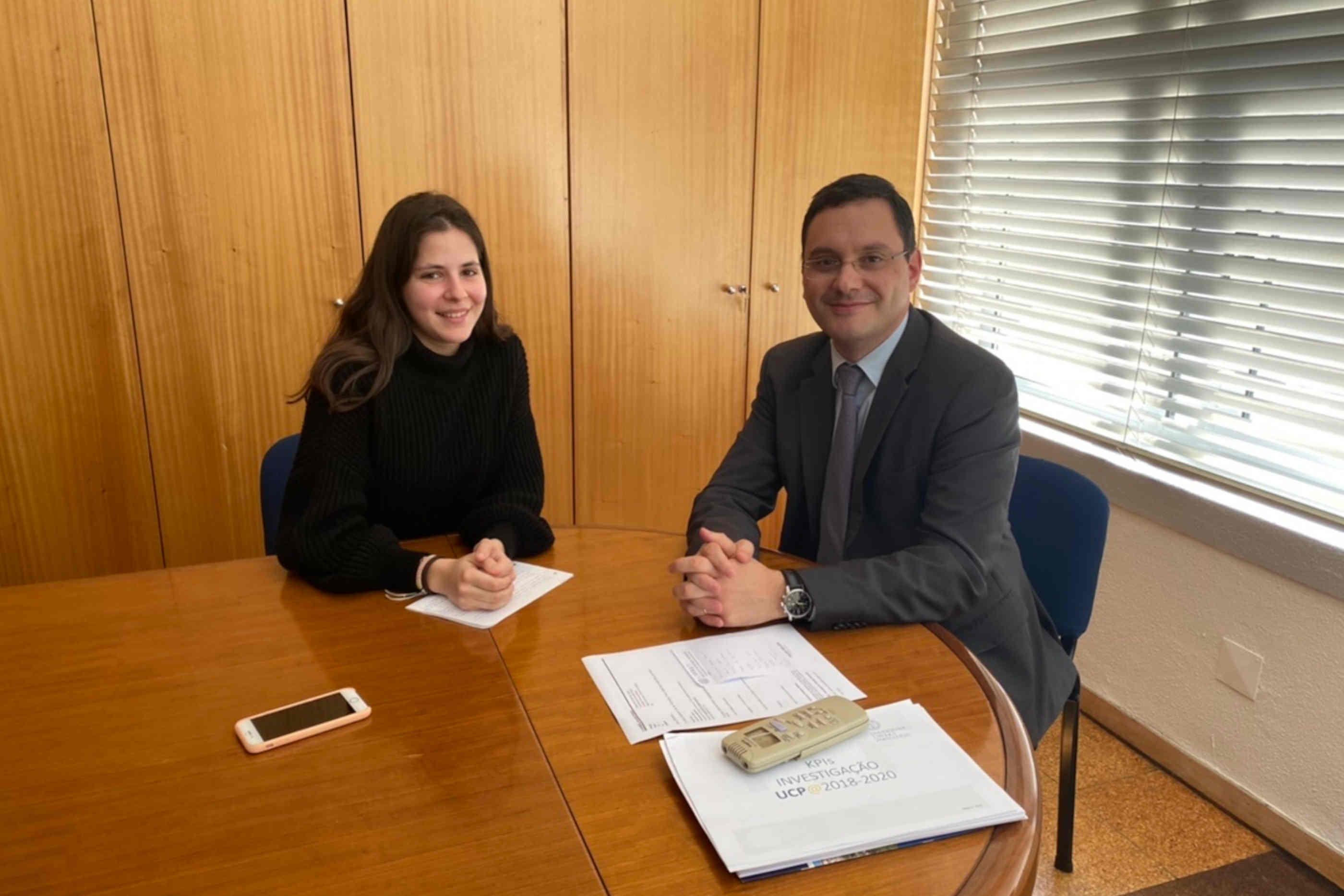 Ana Laura e Professor Nelson Ribeiro, ambos a sorrir, sentados junto à secretária do gabinete deste último.