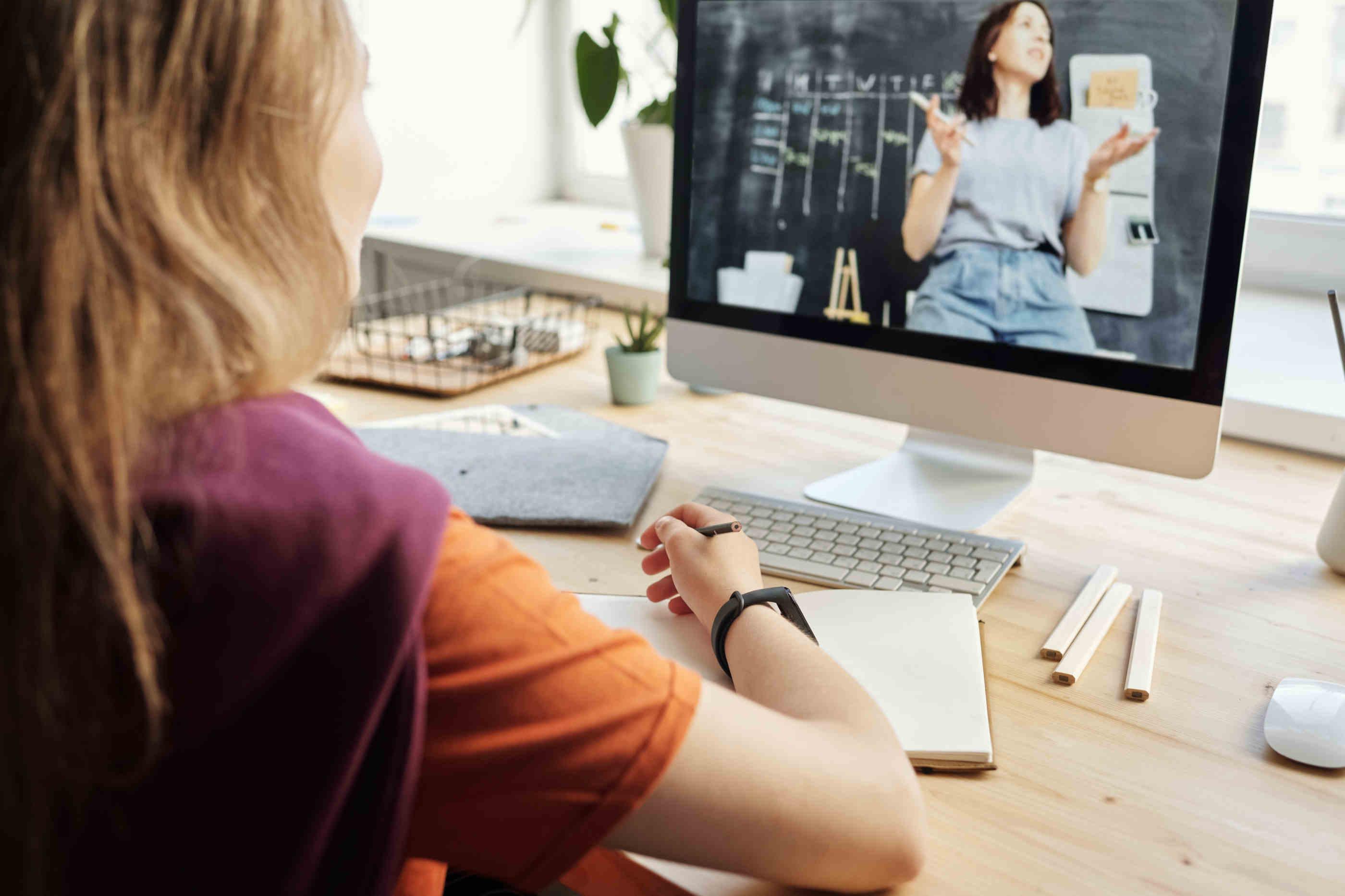 Rapariga a assistir a uma aula online pelo computador enquanto escreve apontamentos.