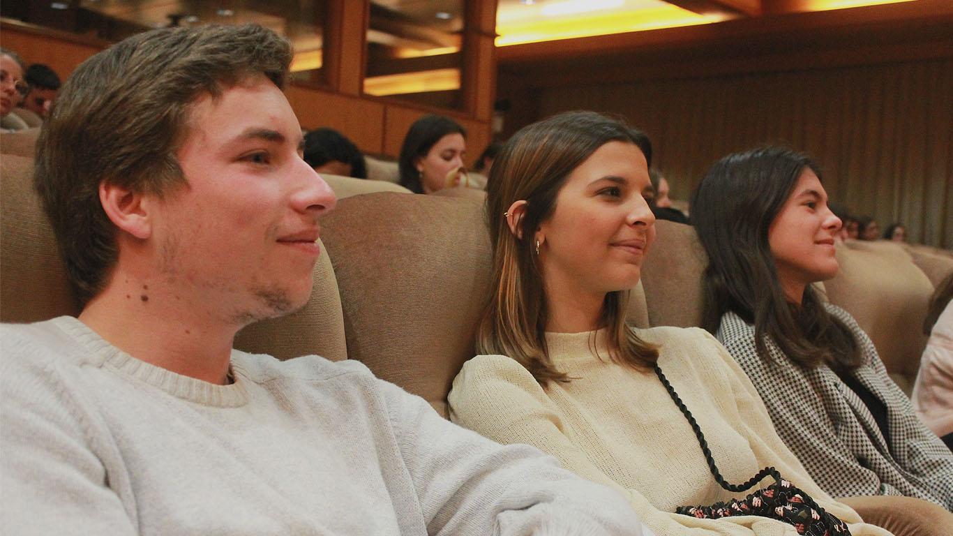 Um rapaz e duas raparigas sentados no auditório a sorrir e atentos ao palco, onde decorre a palestra