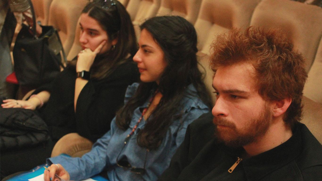 Três alunos recebem a informação transmitida pelos oradores do MyCareer enquanto observam a apresentação