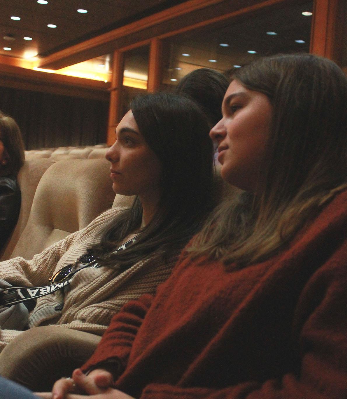 Duas alunas olham serenamente para o palco, assistindo à palestra que decorria no momento