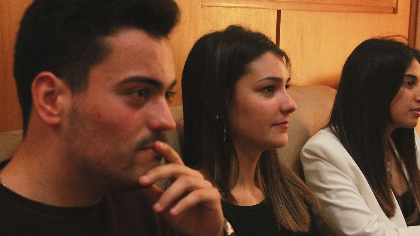 Um rapaz e duas raparigas sentados no auditório Cardeal Medeiros com expressão focada na palestra