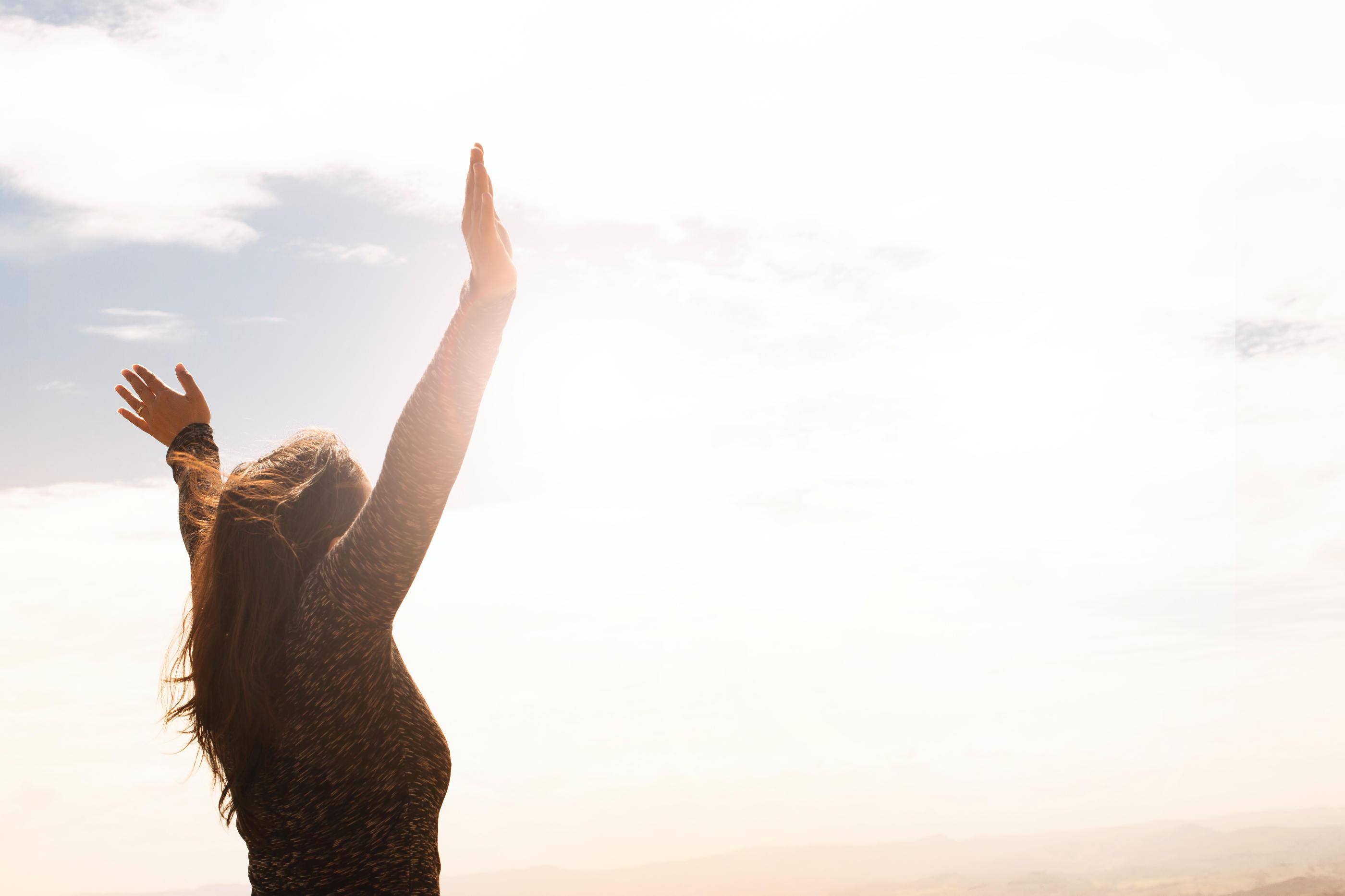 Rapariga com os braços no ar enquanto olha para o céu.