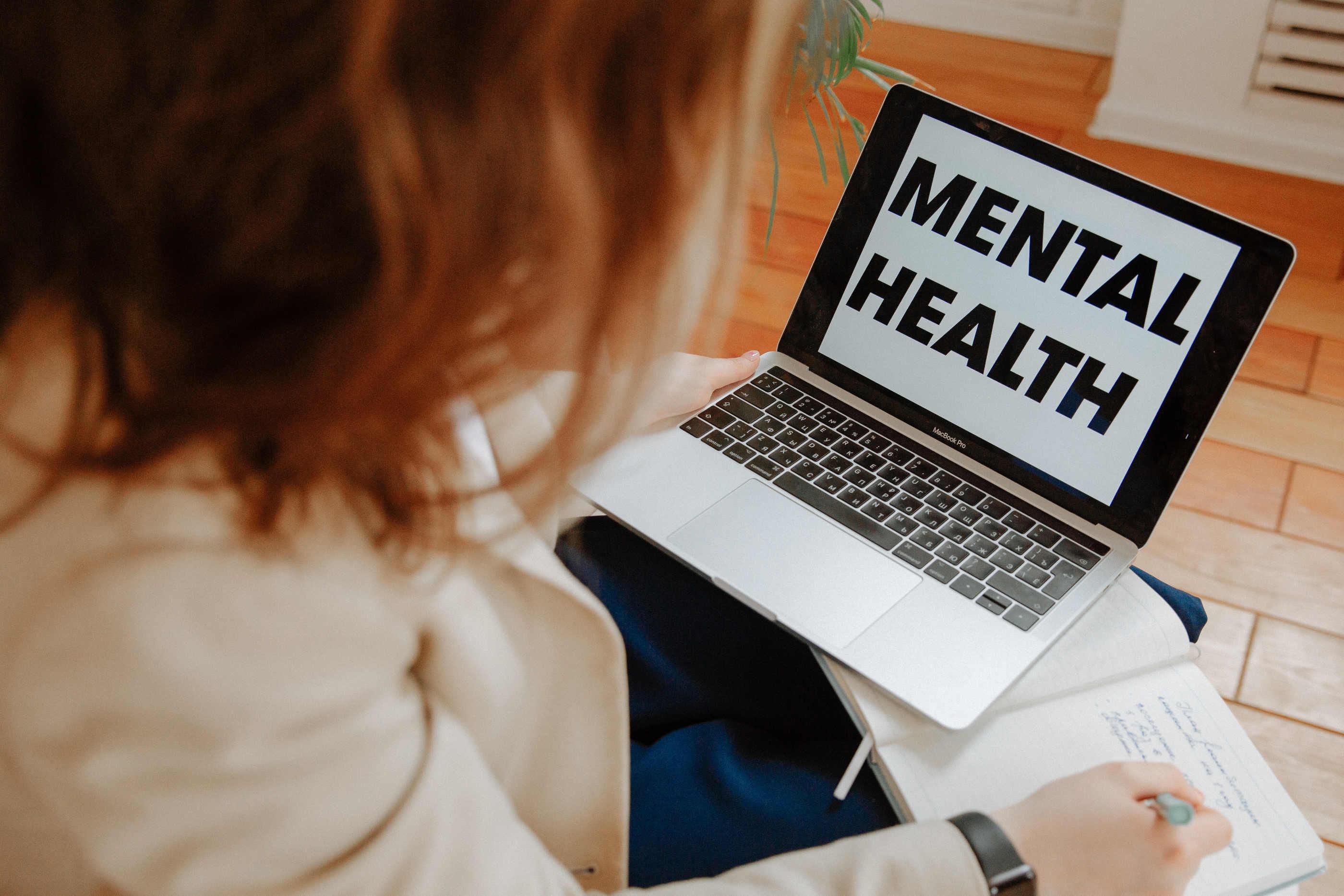 """Rapariga a escrever num caderno em frente a um computador, sendo a imagem de fundo a frase """"Mental health"""""""