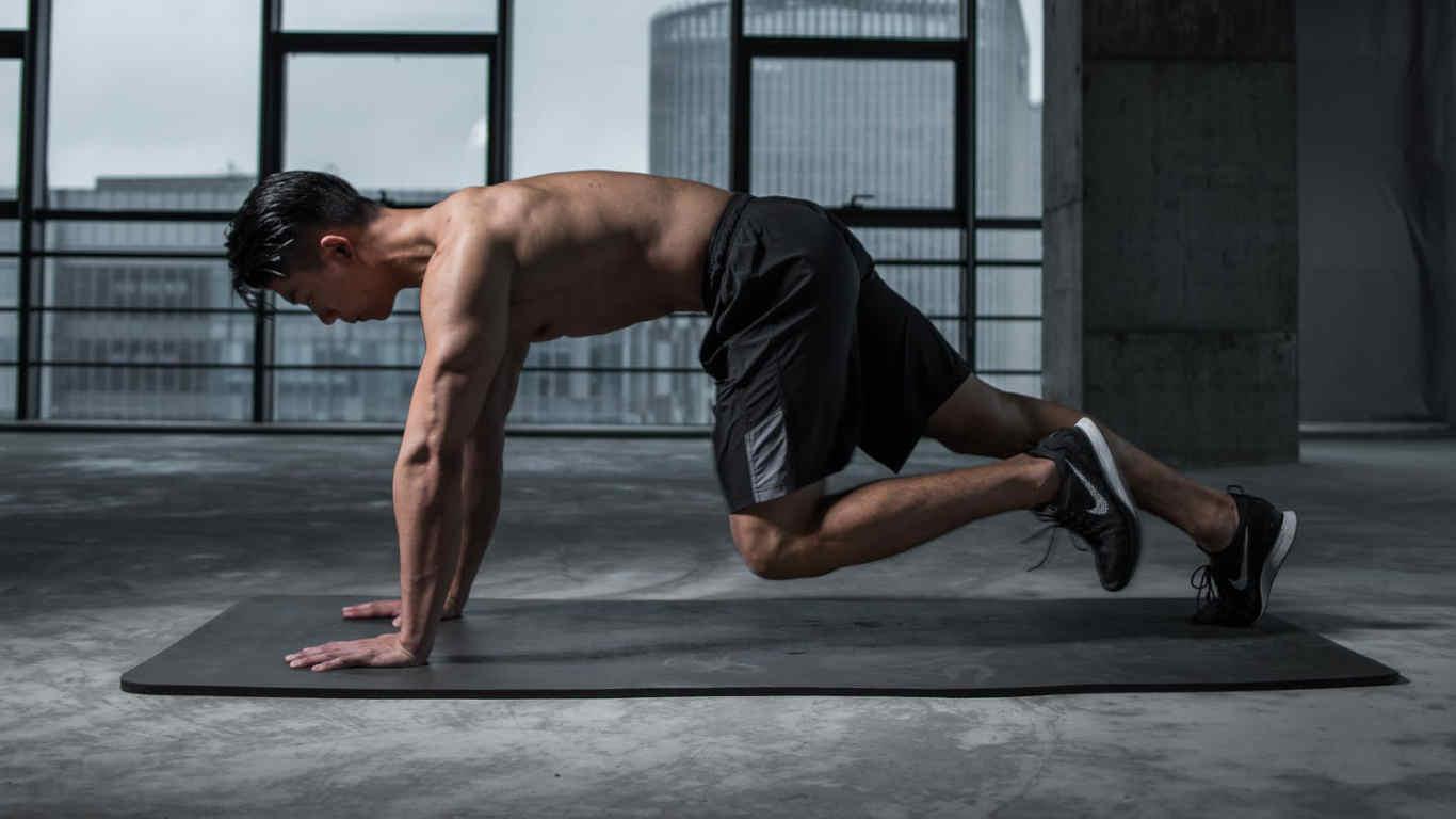Rapaz a fazer exercício físico, de calções, num tapete de fitness