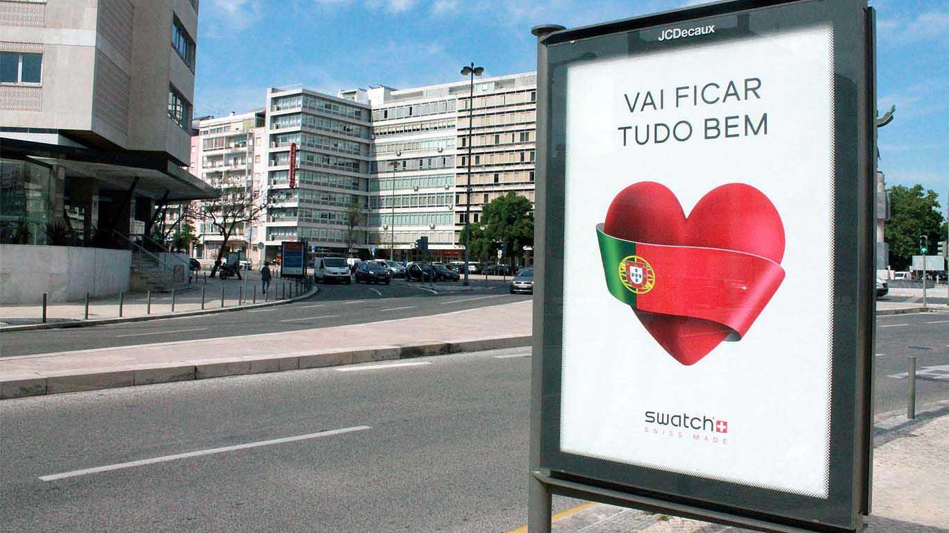 """Placard publicitário da Swatch diz: """"Vai ficar tudo bem"""" e na rua já se vê algum movimento"""