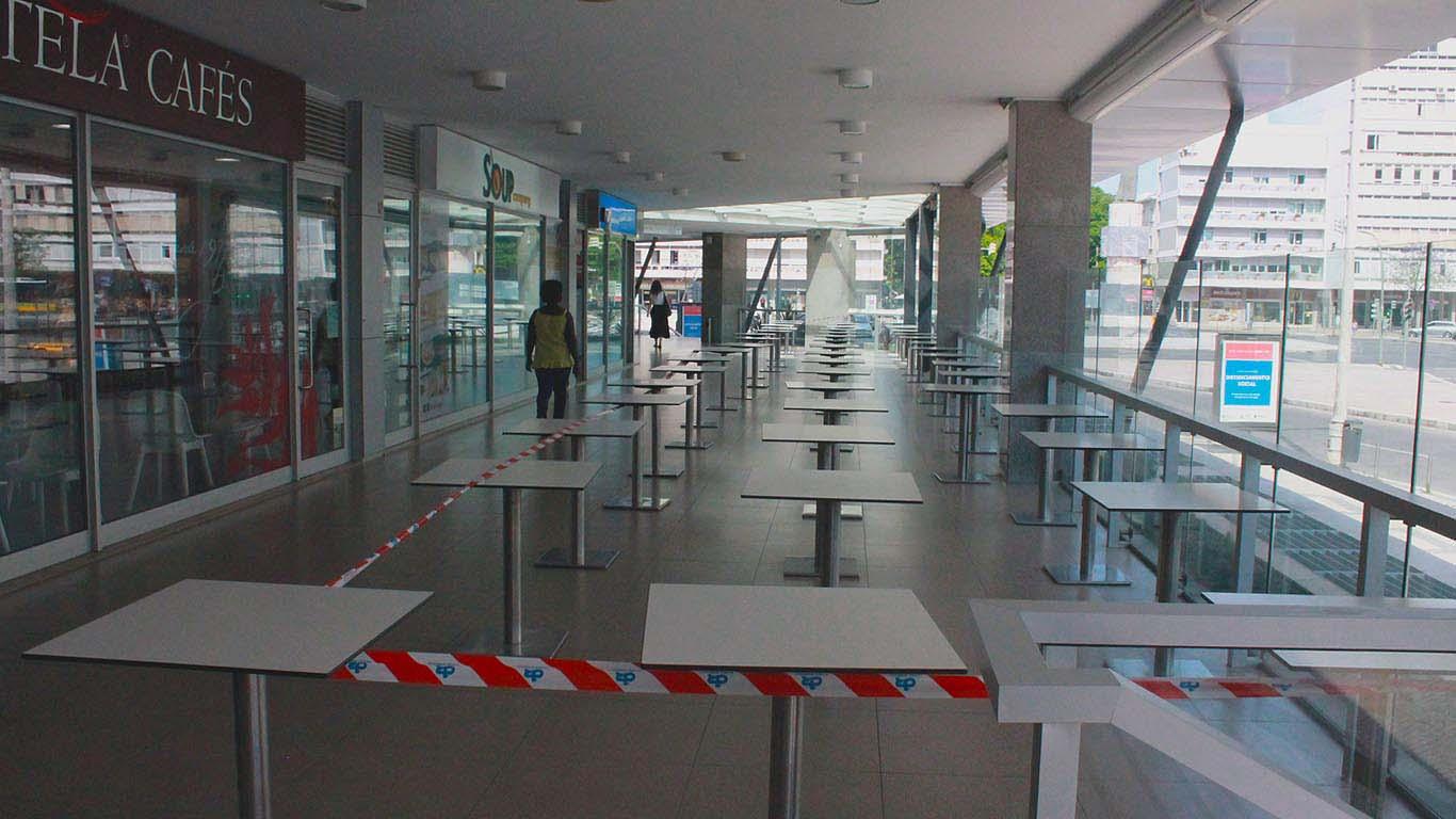 """Zona de restauração de um centro comercial com as mesas encerradas ao público e cercadas com fita que diz """"não passar"""""""