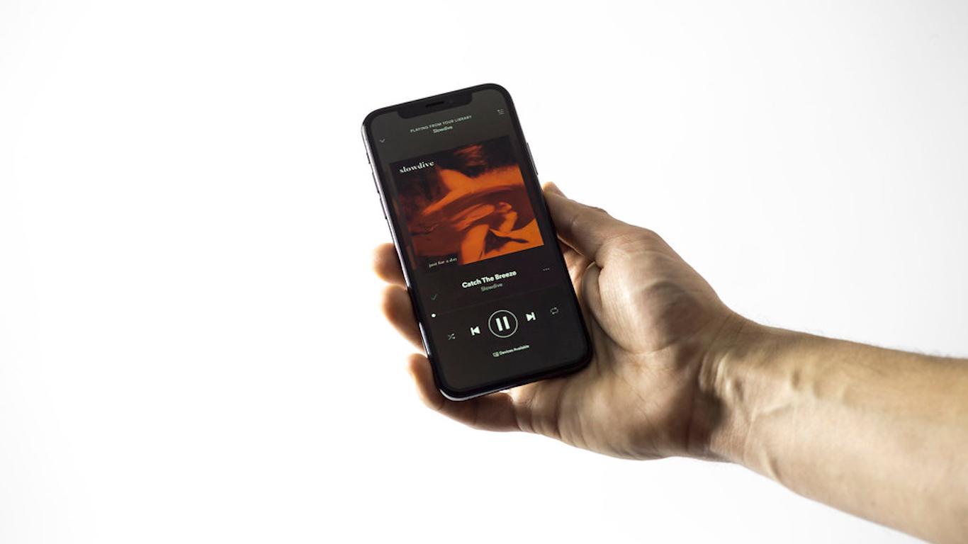 Pessoa a segurar telemóvel com leitor de música