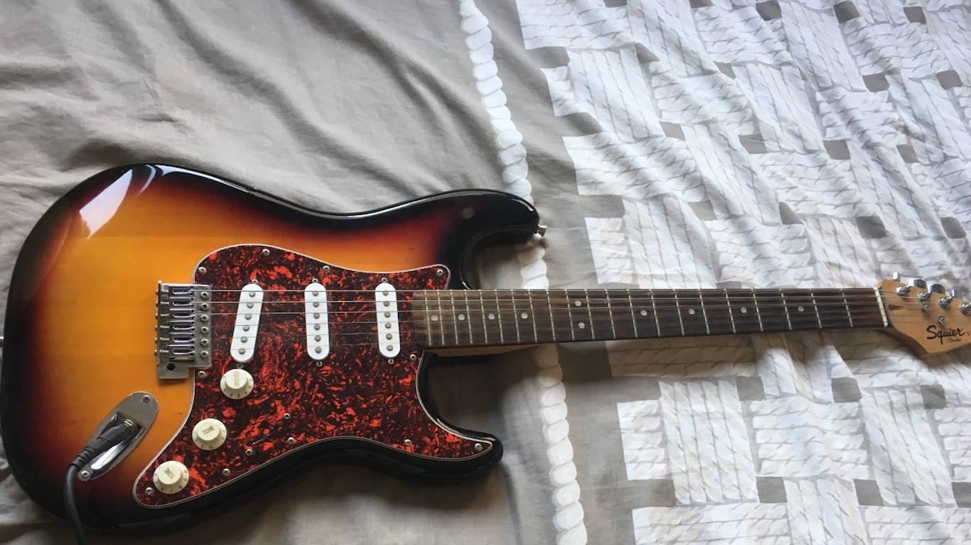 Guitarra elétrica castanha Stratocaster em cima de uma cama