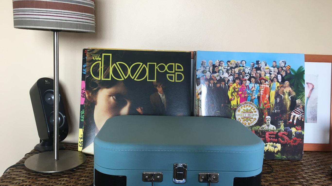Caixa de gira discos Swingson azul com um disco vinil de The Doors e outro de Beatles no fundo, e um candeeiro e uma coluna de som à esquerda.