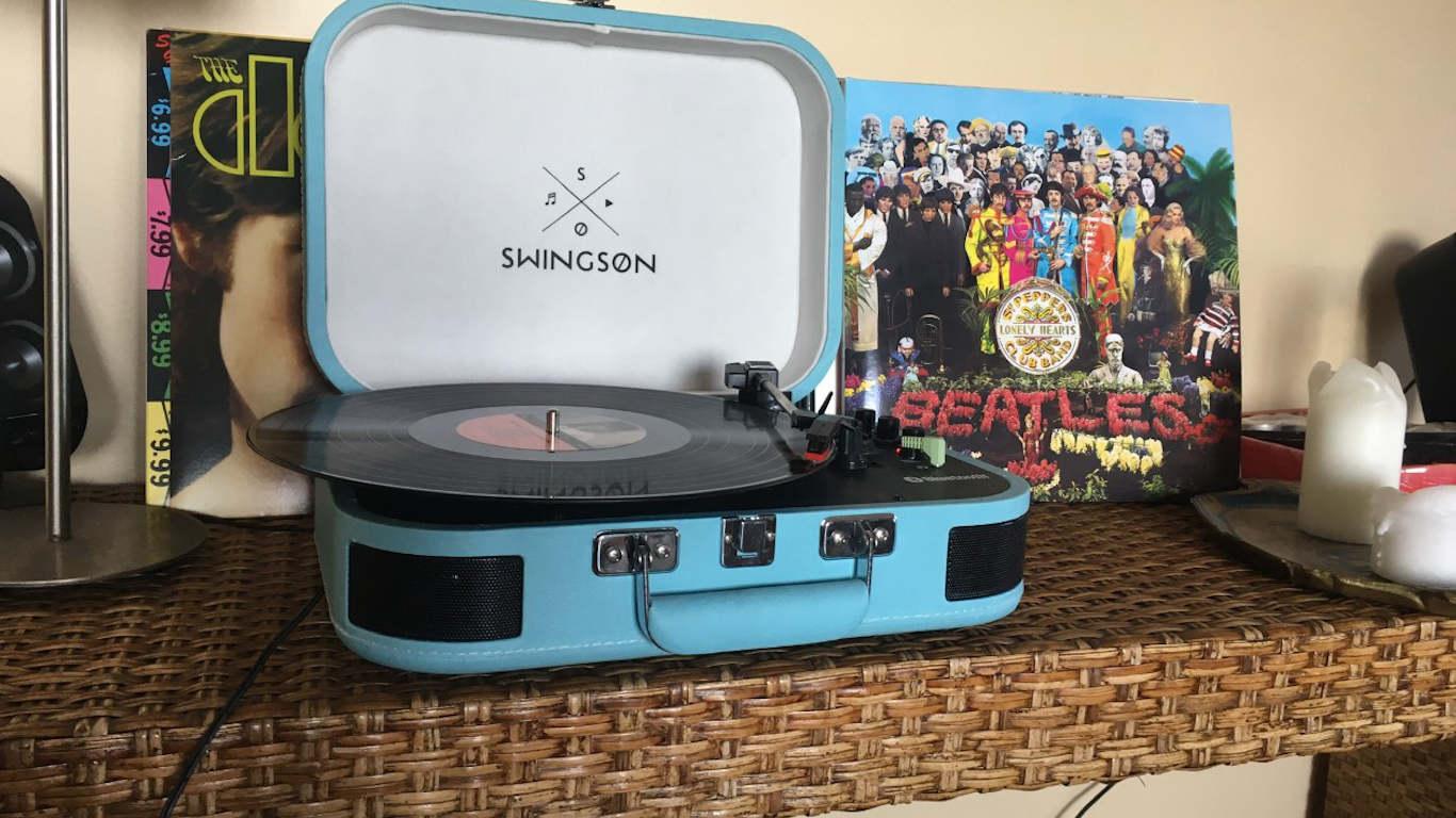 Gira discos azul Swingson com vinil inserido, com vinil de The Doors e outro de Beatles no fundo.