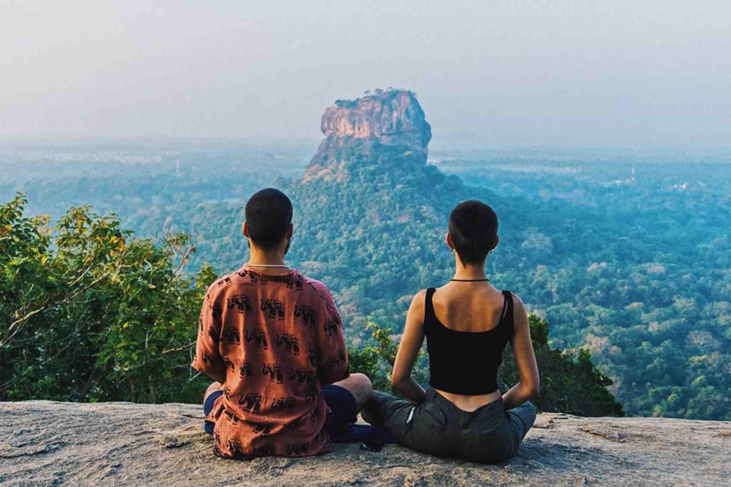 Rapaz e rapariga sentados de costas no topo de montanha com vista verdejante