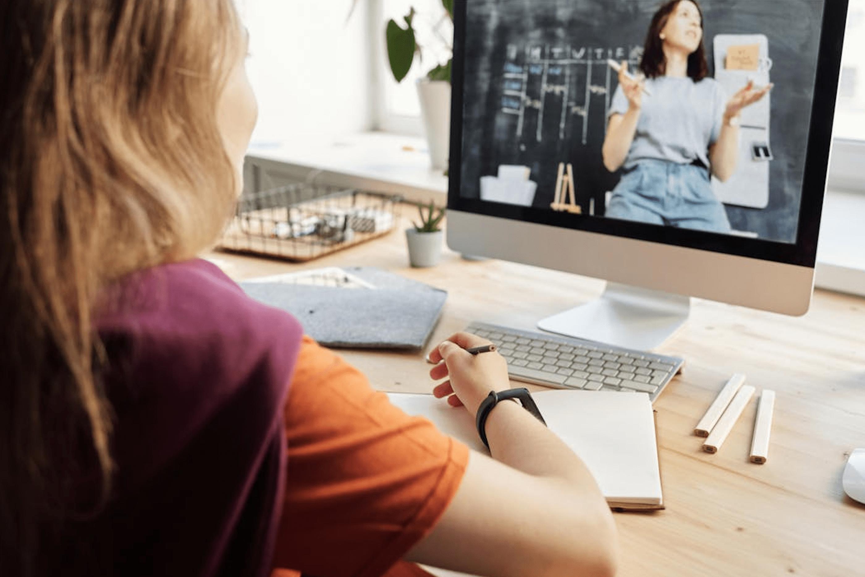 Rapariga a assistir a uma videoaula, no seu computador. Tira apontamentos para o seu caderno.
