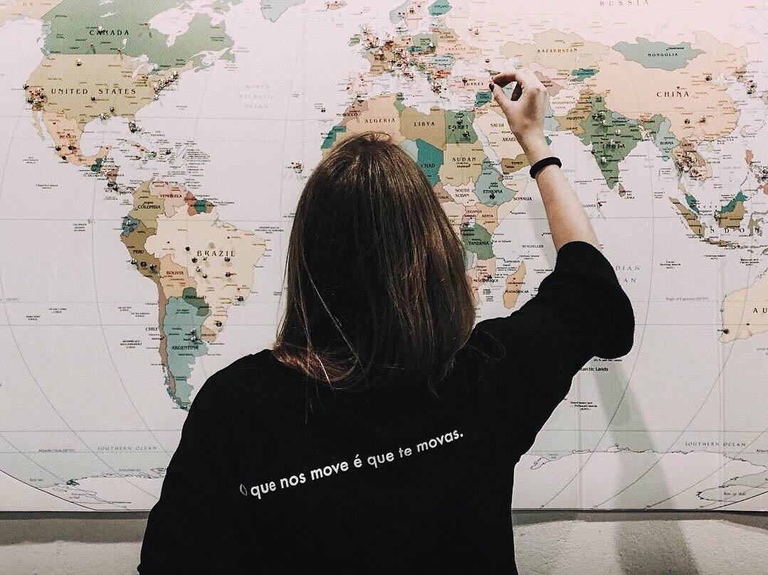 Rapariga com T-shirt preta de costas com mapa mundo de fundo