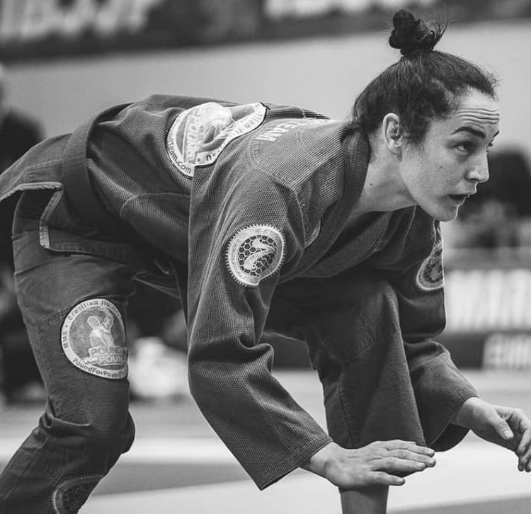 A atleta encontra-se a focar o adversário e adota uma postura com pernas contraídas e costas paralelas ao chão
