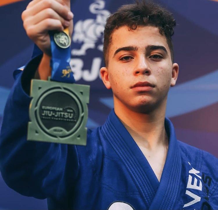 Jovem atleta segura na sua mão a medalha que consagra mais uma das suas vitórias.