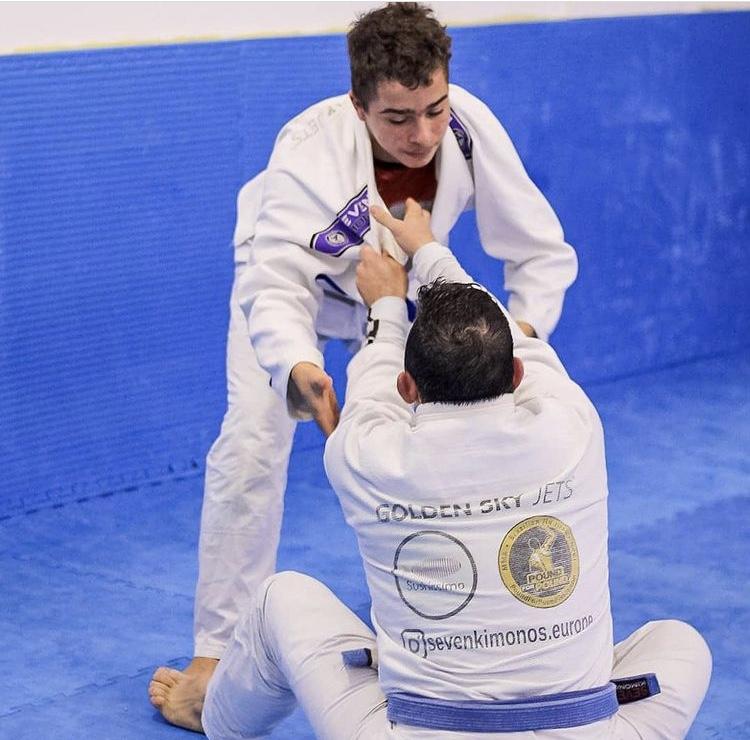 Dois praticantes de jiu-jitsu de idades distintas numa posição de jiu-jitsu denominada de guarda aberta.