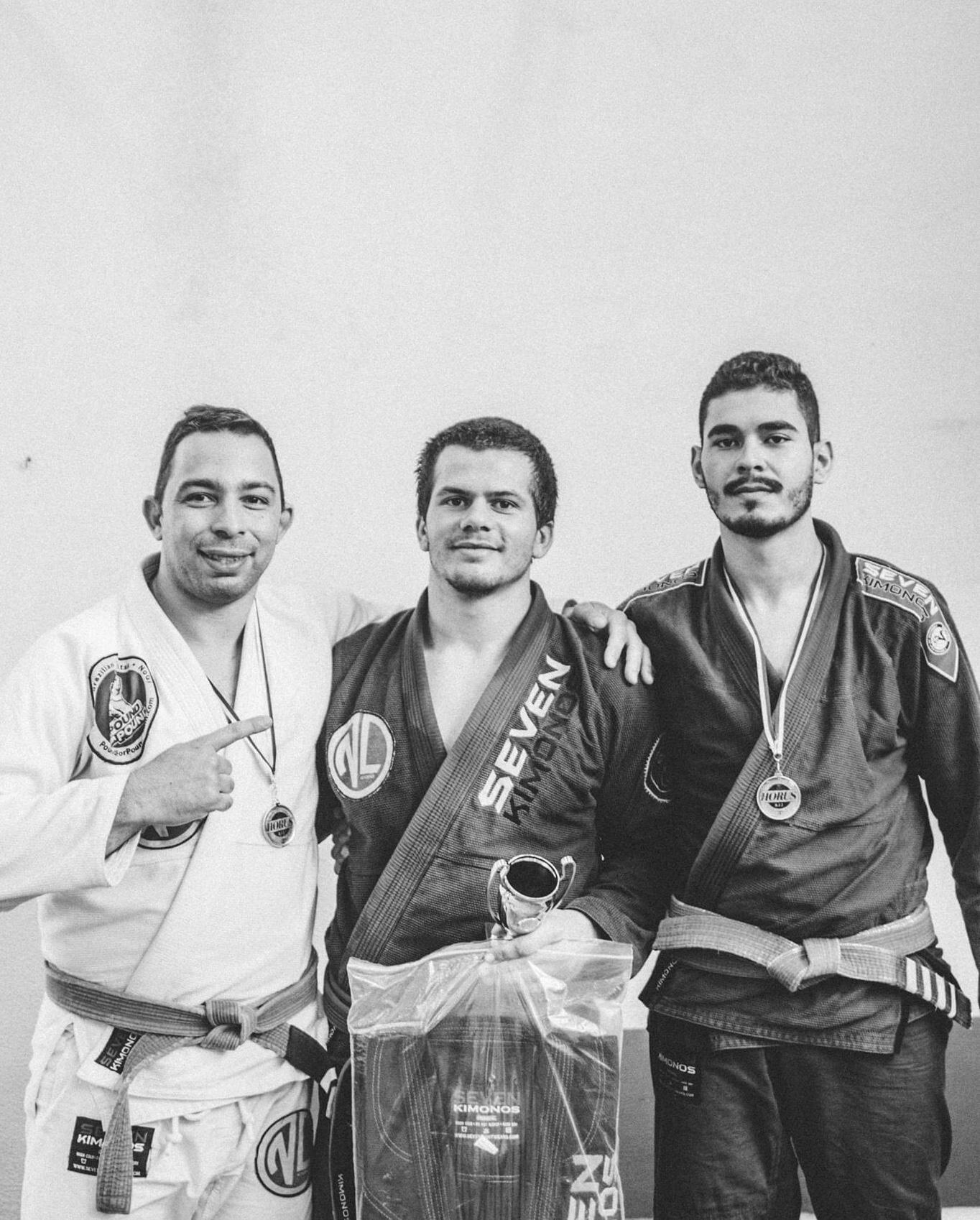 Três atletas felizes abraçados com duas medalhas ao pescoço e um troféu na mão.