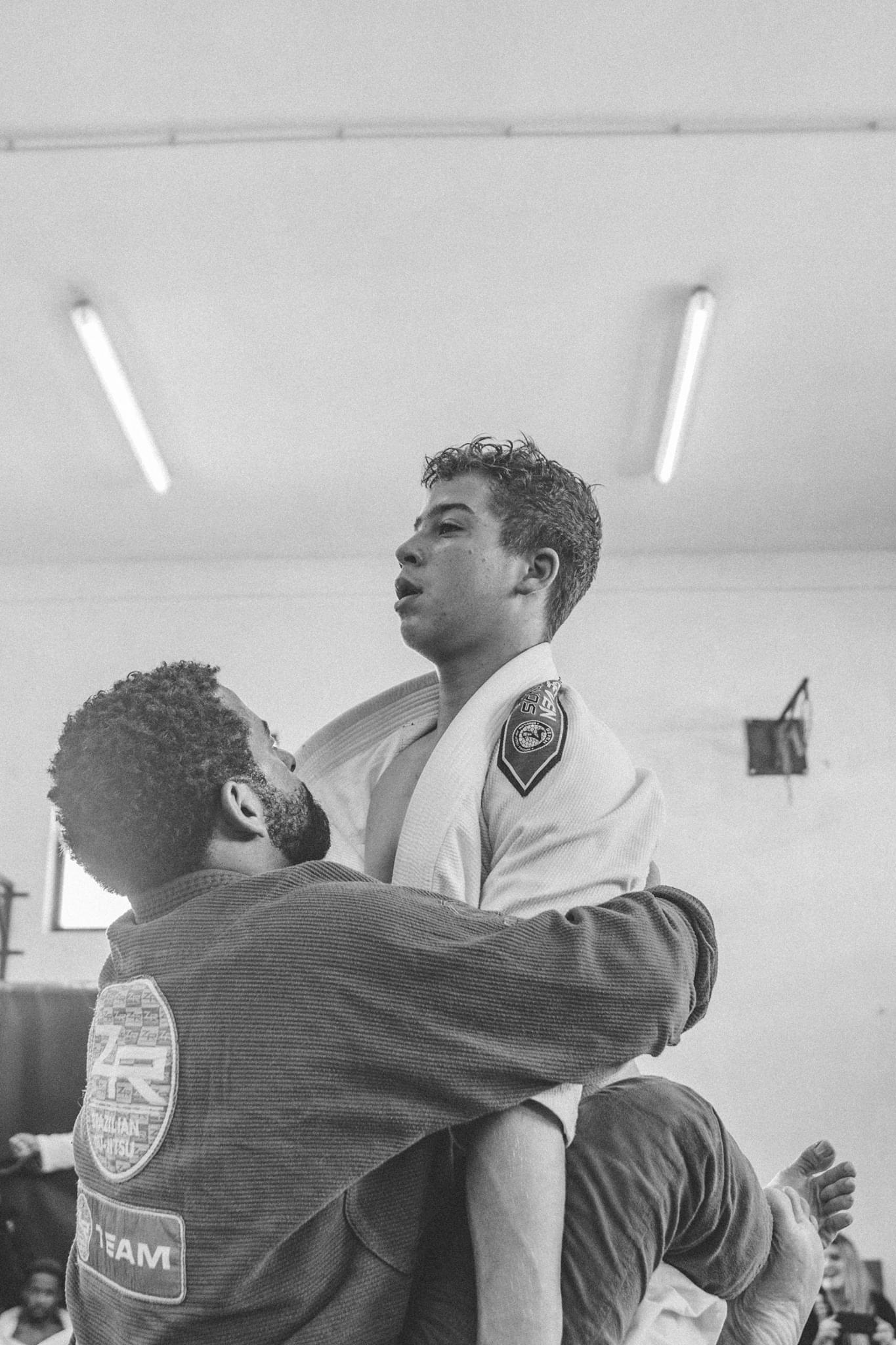 Dois membros da mesma equipa, em fase de treino, em que um deles exerce força sob o outro, impedindo-o de exercer qualquer movimento, ao prender lhe os braços.