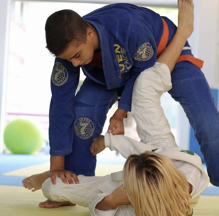 Dois atletas de géneros opostos, em que o rapaz veste um kimono azul e a rapariga um kimono branco, praticam a posição de passagem de guarda aberta.