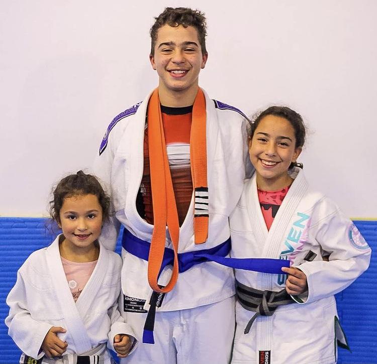 Três atletas sorridentes abraçados