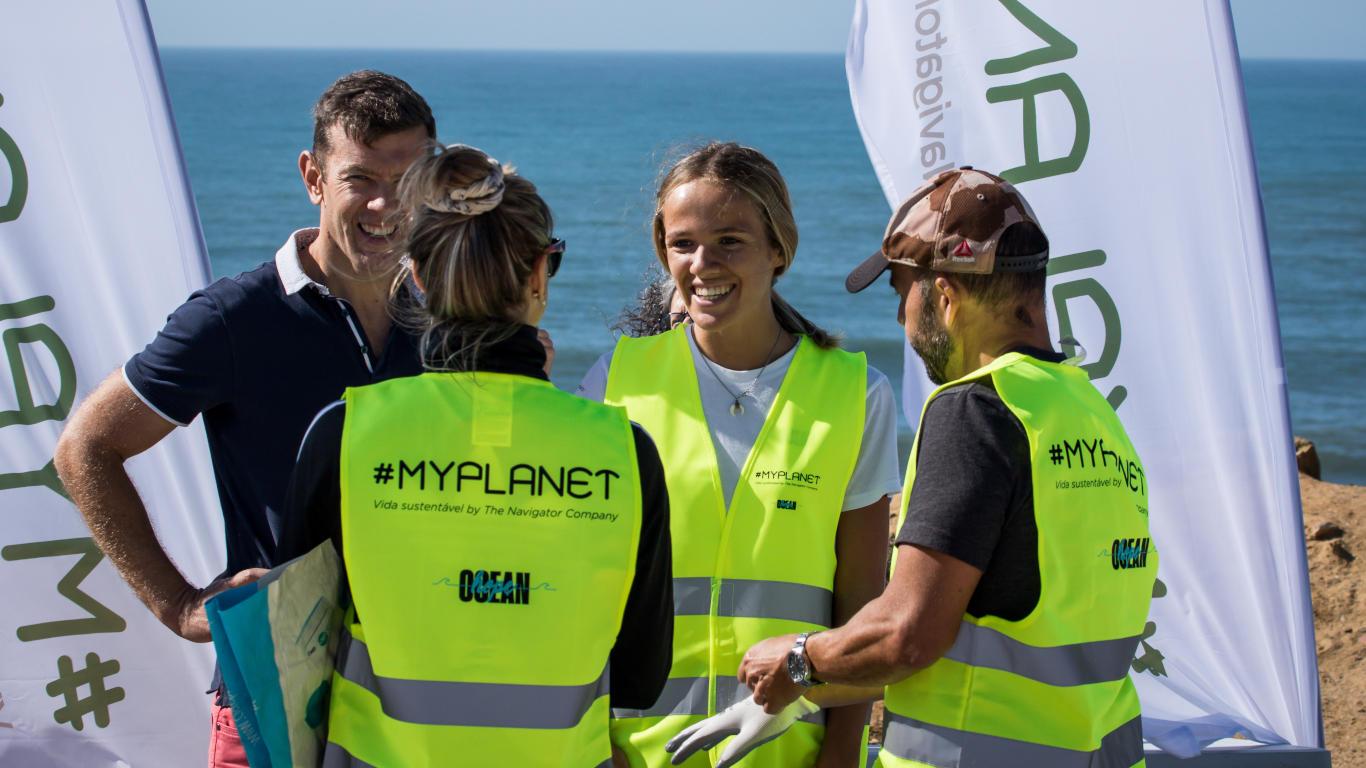 Imagem captada no exterior perto do mar, na qual está presente um grupo de pessoas a falar e a rir.