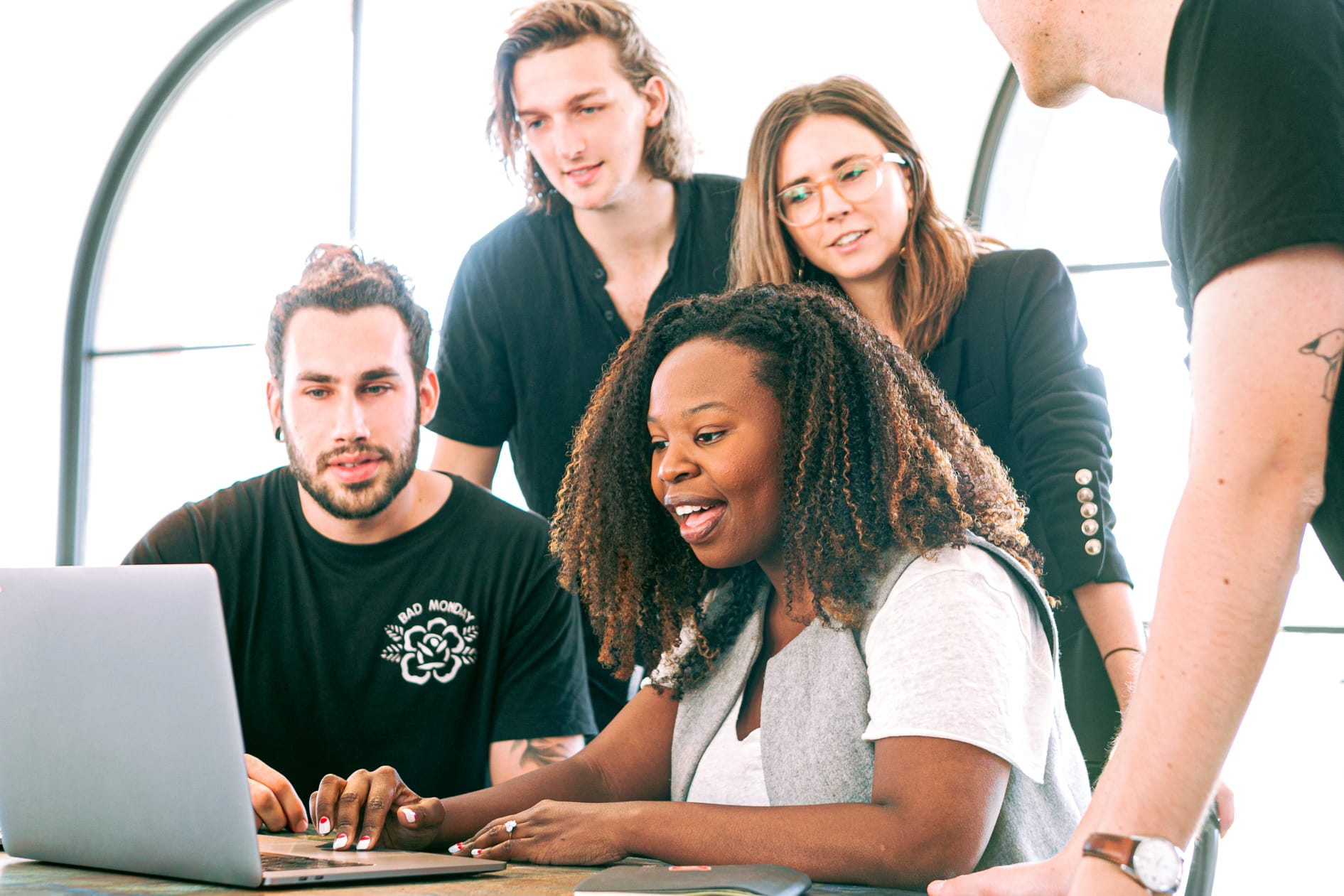 Grupo de estudantes motivados a trabalhar em conjunto. Encontram-se à volta de um computador.