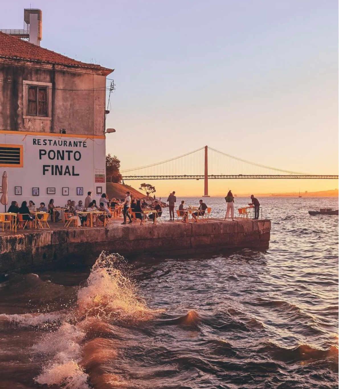 Vista da esplanada do restaurante Ponto Final, em Cacilhas. Vemos o pôr do sol com a ponte 25 de Abril ao fundo.