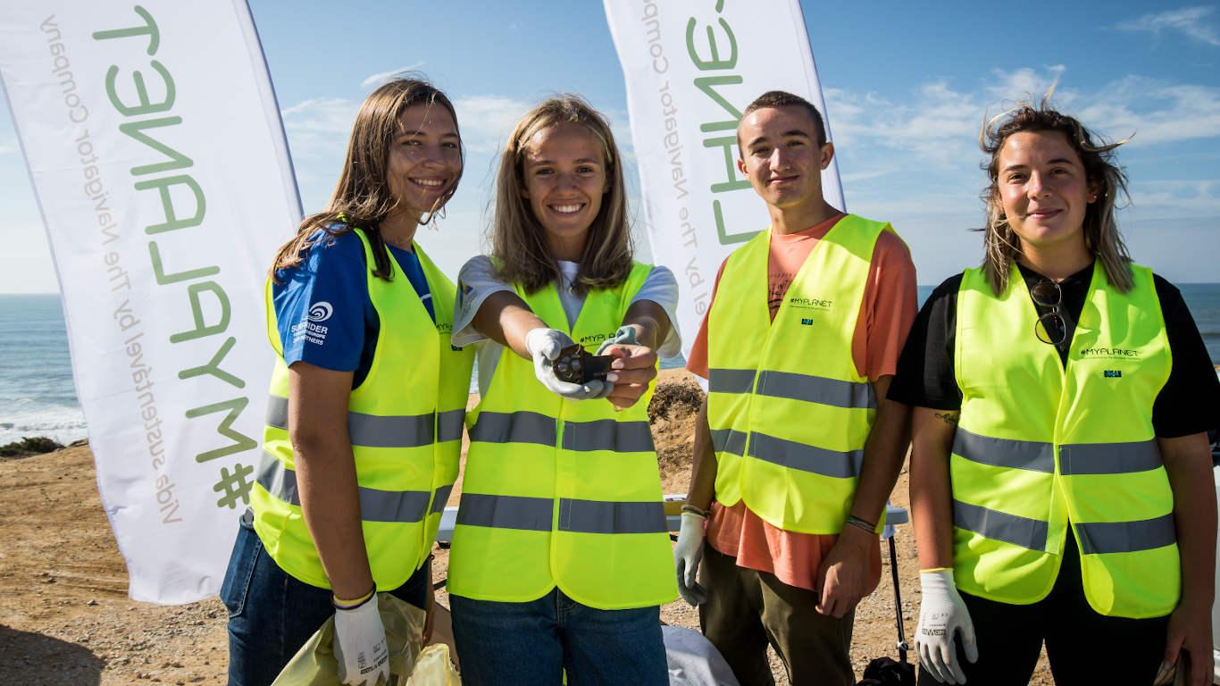 Imagem de um grupo de adolescentes sorridentes, com a presença de bandeiras no plano de fundo.
