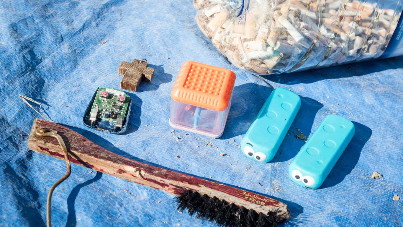 Fotografia de uma escova, itens de plástico e beatas de cigarro, recolhidos na praia.