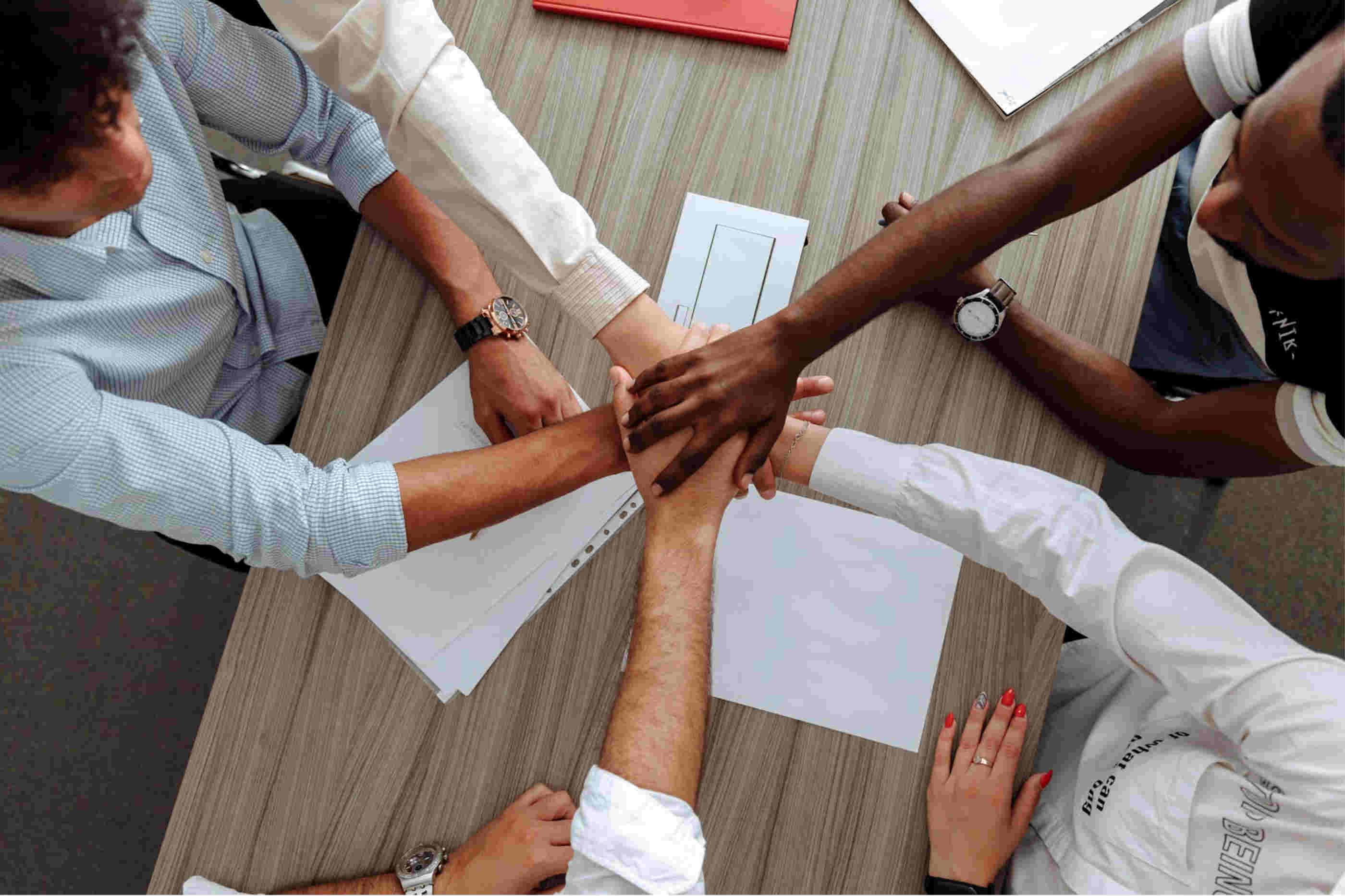 Cinco jovem unem as mãos como símbolo de motivação