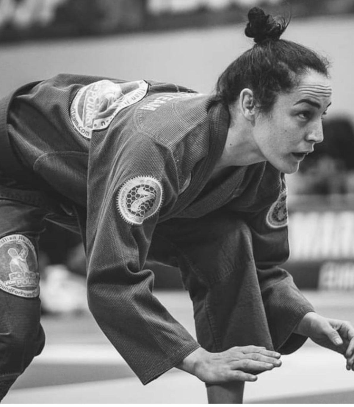 A atleta encontra-se a focar o adversário e adota uma postura com pernas contraídas e costas paralelas ao chão.
