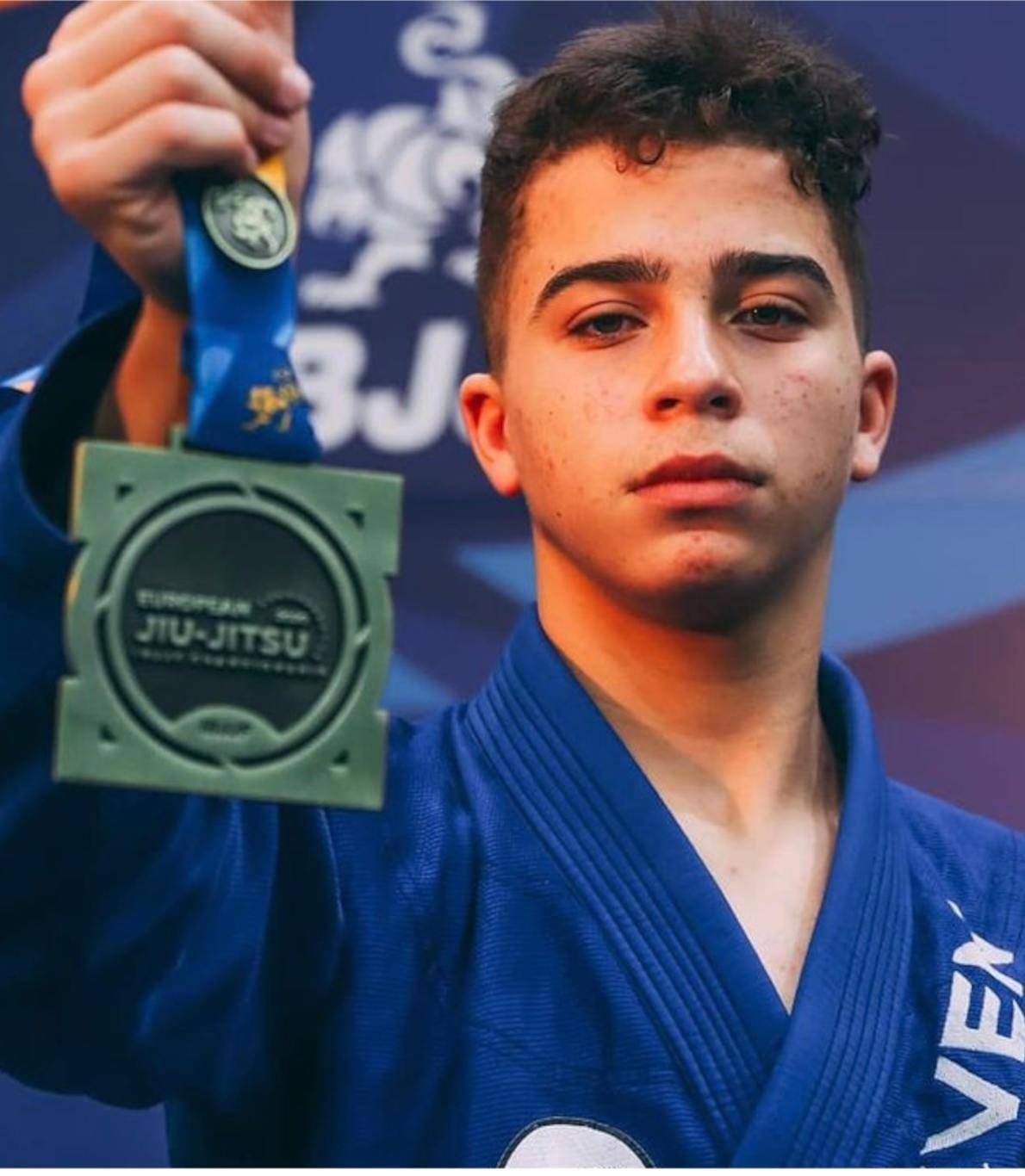 Jovem atleta que veste um kimono azul, segura na sua mão a medalha que consagra mais uma das suas vitórias.