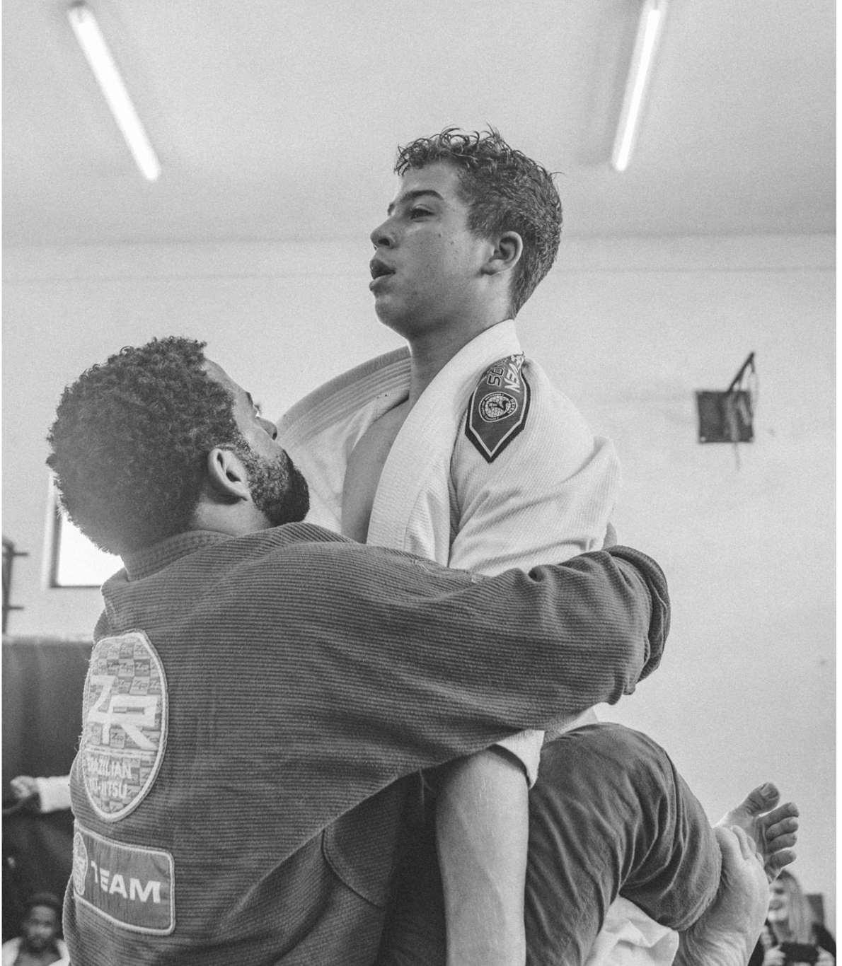 Dois membros da mesma equipa, em fase de treino, em que um deles exerce força sob o outro, impedindo-o de exercer qualquer movimento, ao prender-lhe os braços.