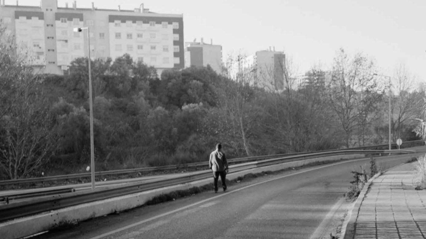 """Fotografia a preto e branco de homem a andar na estrada. Uma das 80 fotografias da exposição """"Ballad Of Today"""""""