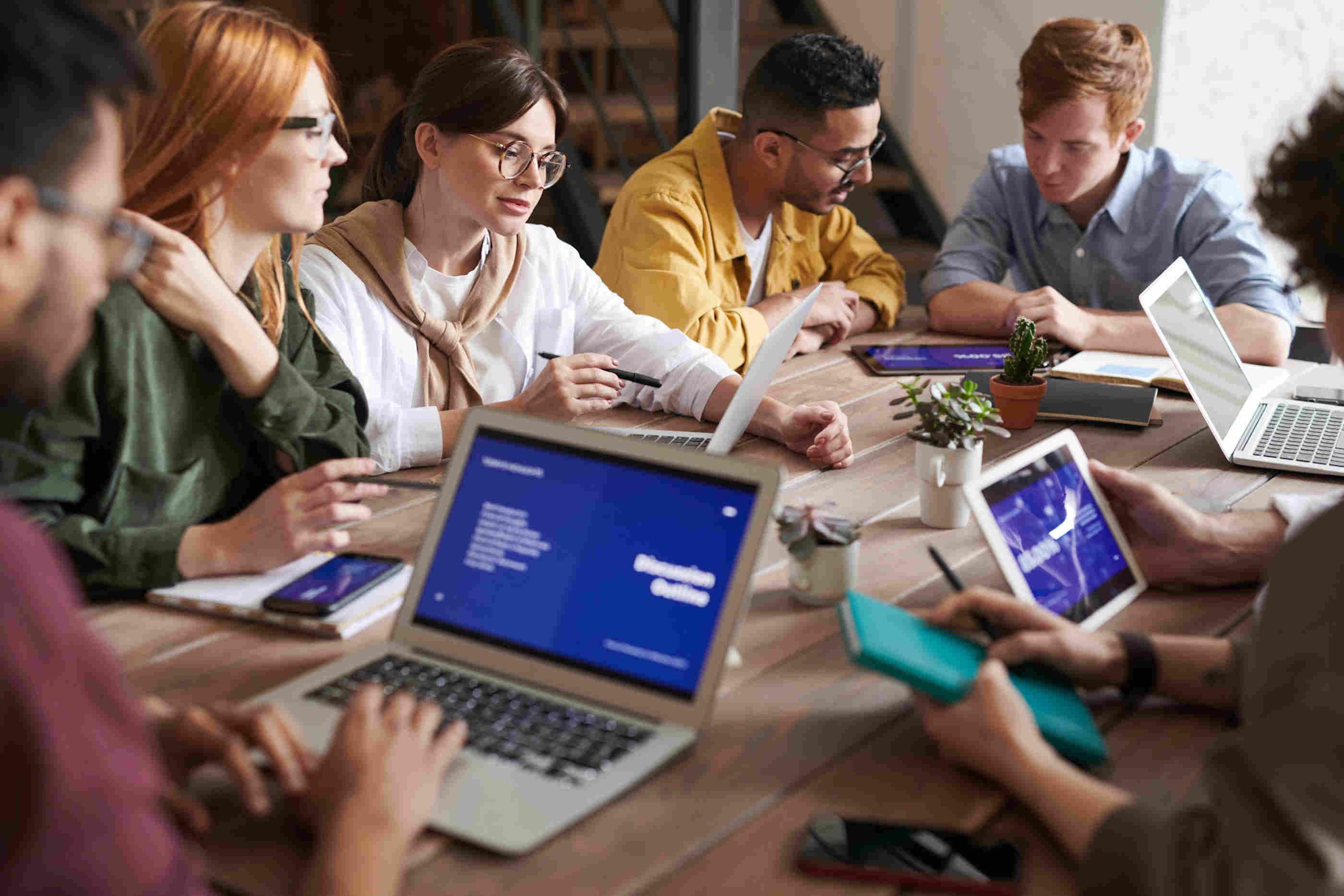 Sete estudantes a trabalhar nos seus computadores e a discutir ideias em conjunto.