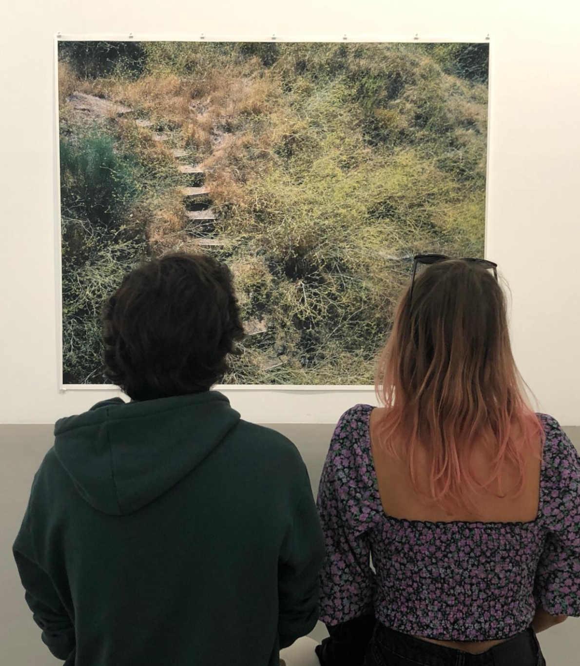 Um rapaz e uma rapariga sentados num banco, lado a lado, a olhar para um quadro