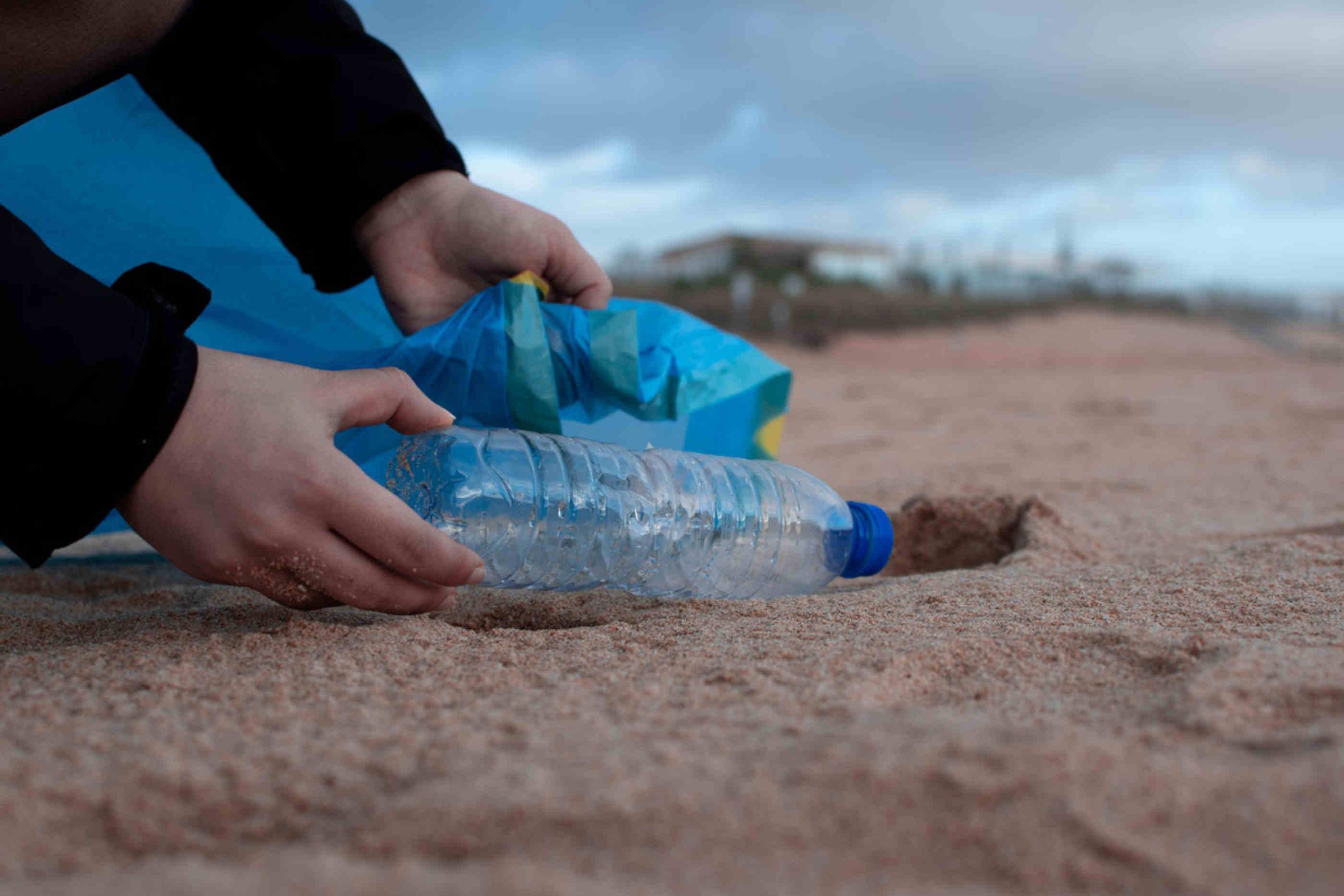 Pessoa colocando garrafa de agua no lixo