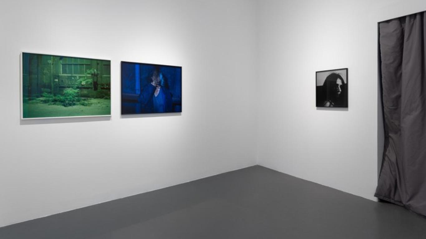 """Uma das salas da exposição """"Ballad Of Today""""- Onde se vêm 3 quadros numa parede branca e um cortinado"""