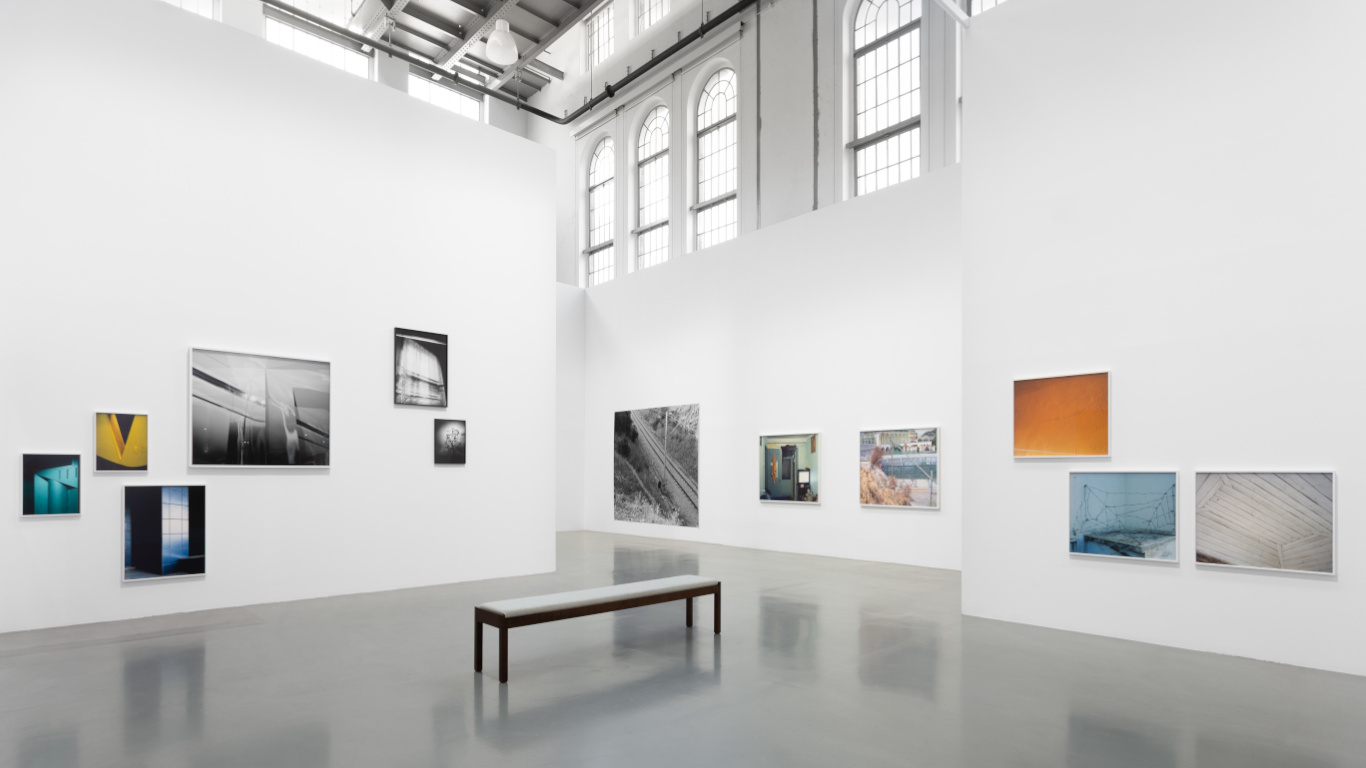 """Uma das salas da Exposição """"Ballad of Today"""" com quadros nas paredes e um banco no centro da mesma"""