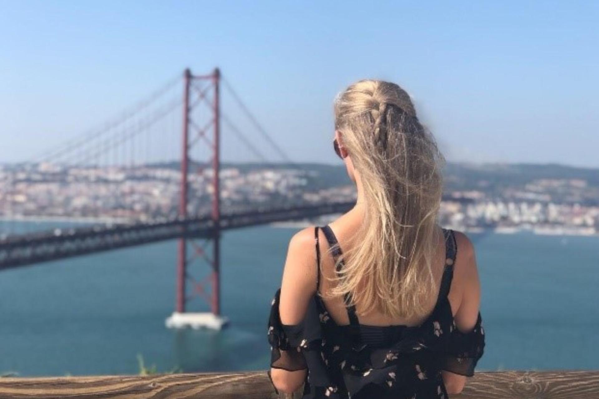 Foto de Lisa Penelope, aluna de Erasmus de costas a olhar para a Ponte 25 de Abril e para o Rio Tejo.