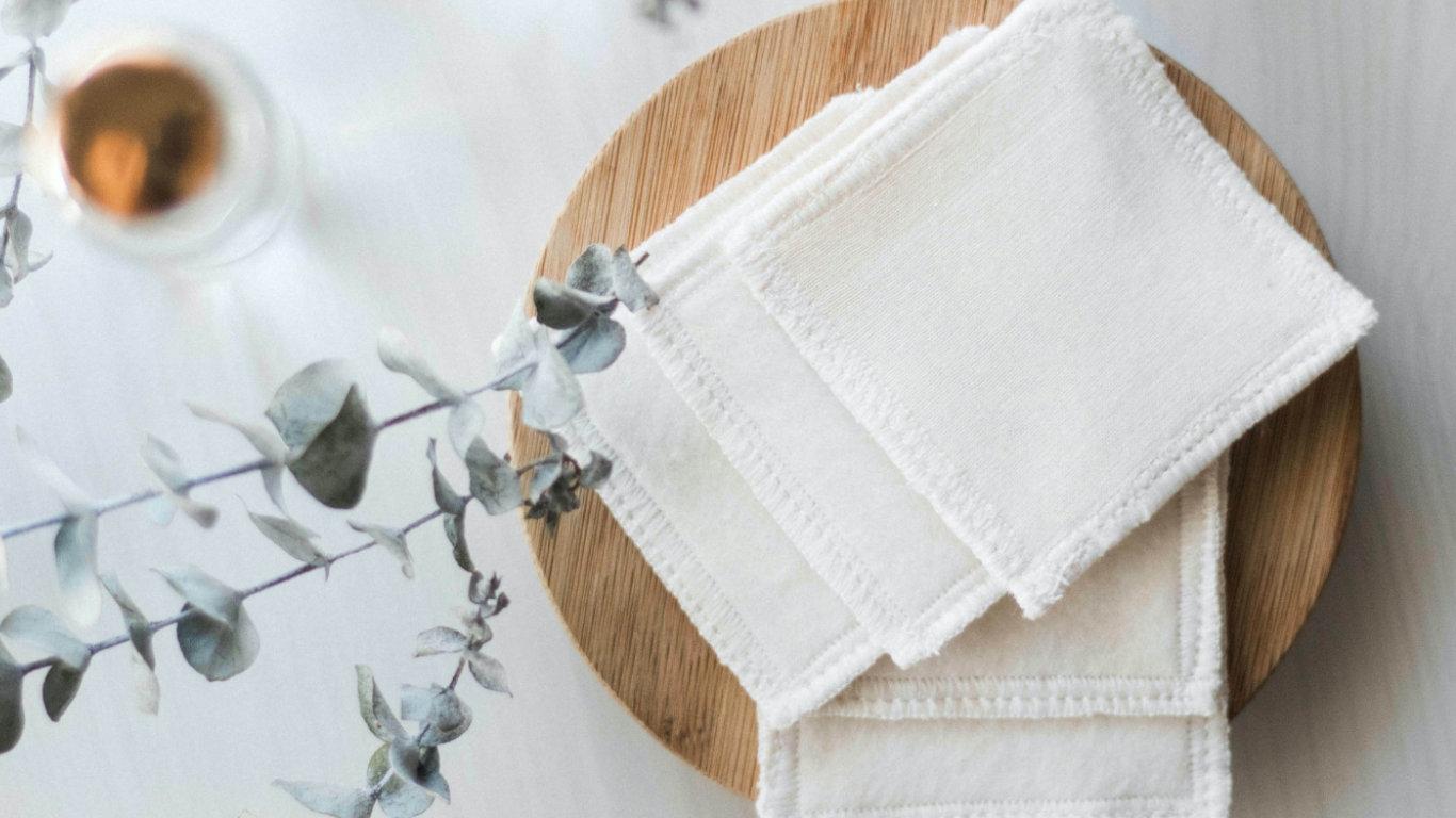 Cinco pedaços de algodão de pano branco, sobrepostos numa tábua de madeira clara. Vê-se parte de uma planta verde.