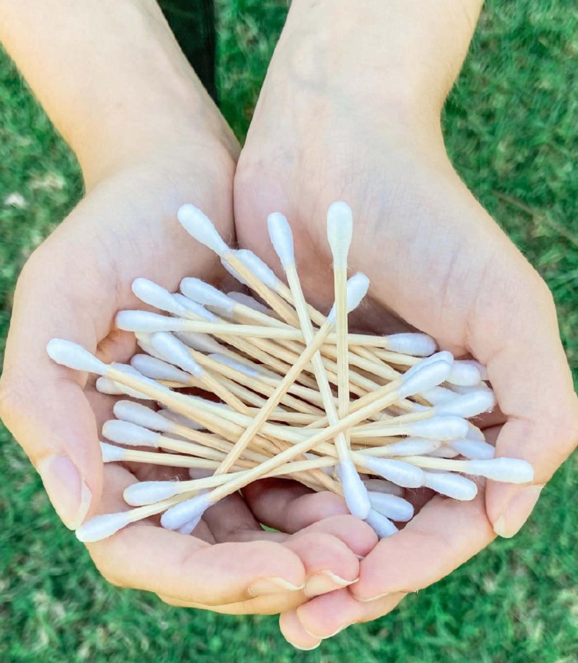 Na imagem vê-se as mãos de uma pessoa abertas em concha, cheias de cotonetes de bambu e de algodão. No fundo dessa imagem, vê-se relva no tom de verde bem vivo.