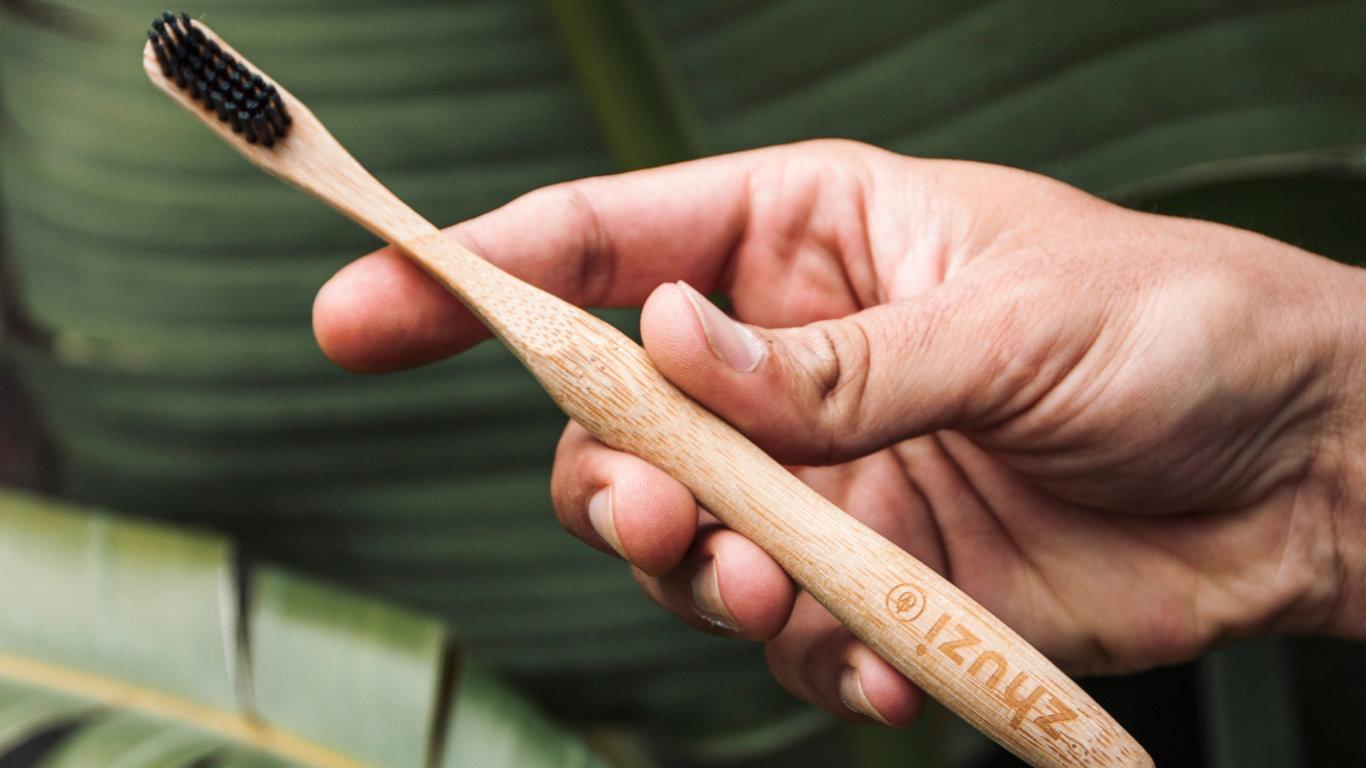 Na imagem observamos ao fundo umas folhas verdes grandes, e uma mão que agarra uma escova de dentes de bambu com cerdas pretas.