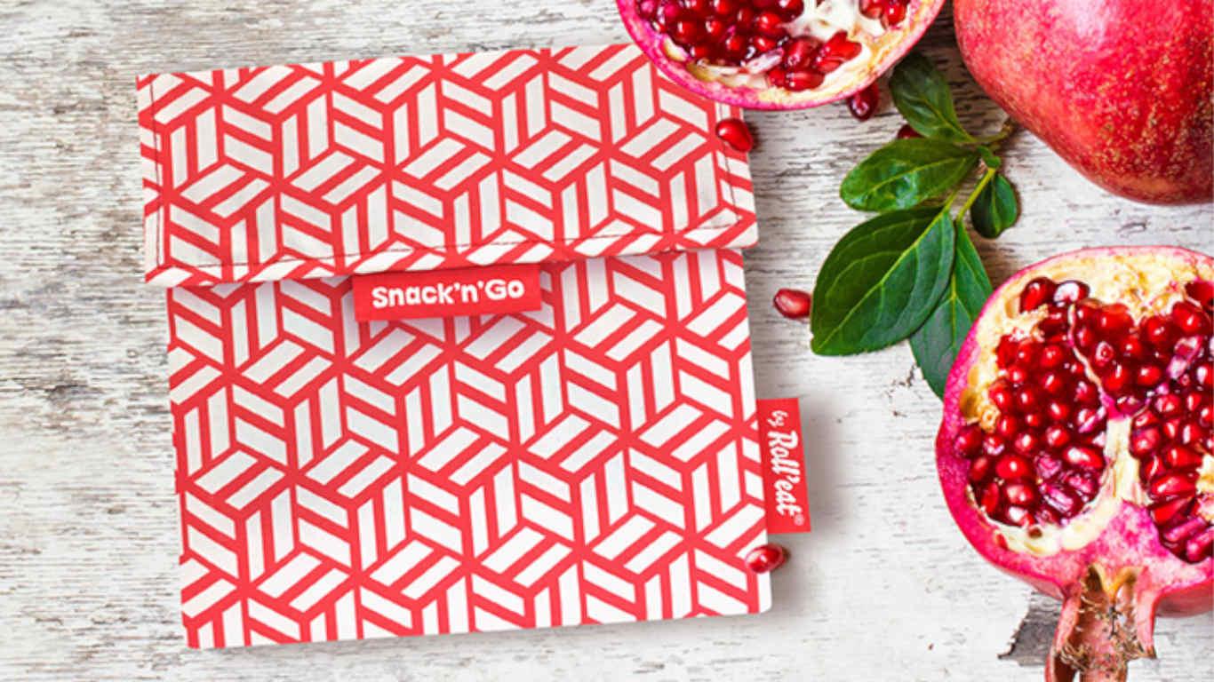 """Bolsa de pano quadrada, com um padrão """"abstrato"""" de cubos branco e vermelho. No lado direito, vê-se uma metade de romã com as suas sementes e bocadinhos mais pequenos de outras duas romãs, como também algumas folhinhas verdes."""