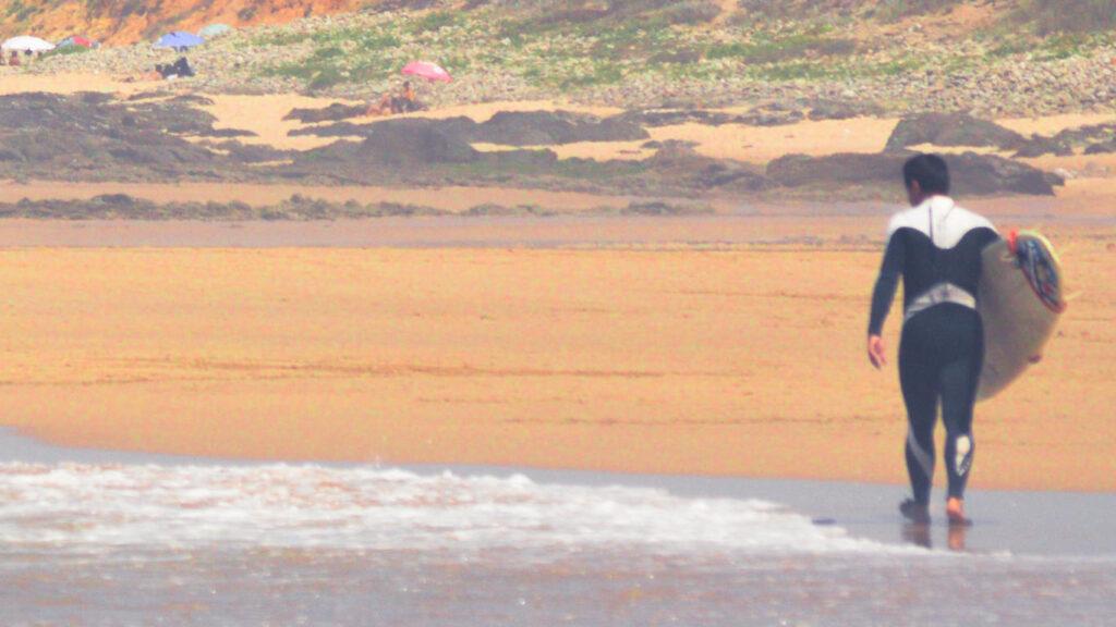 Surfista com prancha na mão, banhistas com guarda-sóis coloridos ao fundo