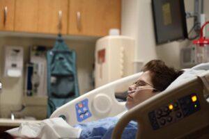 Homem deitado numa cama hospital.
