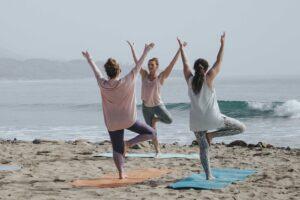 3 mulheres exercício de yoga praia