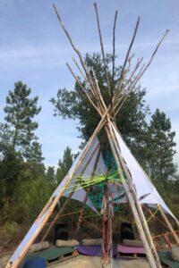 tenda tipo cone de madeira e com um pano branco no meio da natureza